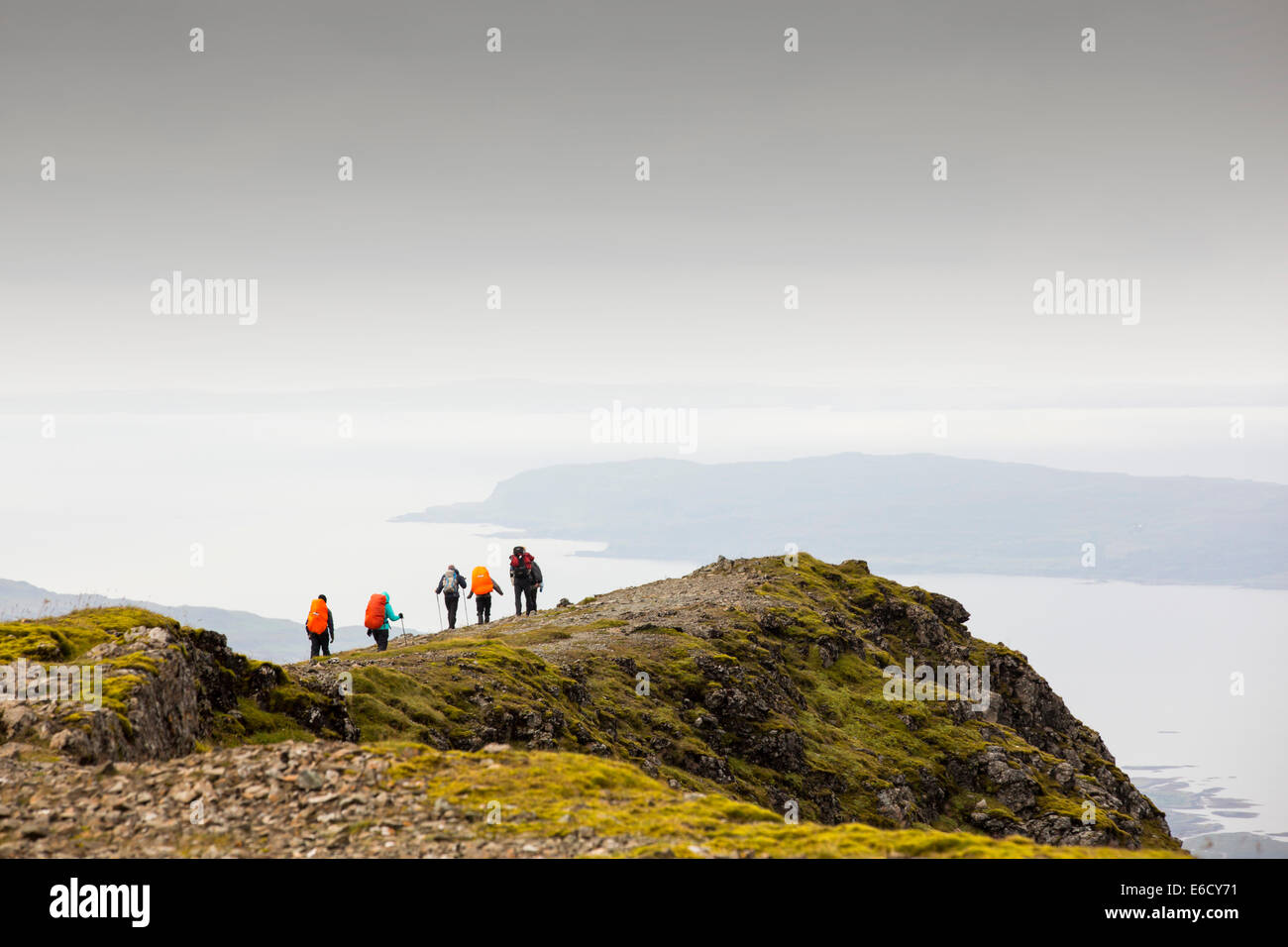 A walking group on the summit of Munro on Ben More, Isle of Mull, Scotland, UK, looking down to loch na Keal. - Stock Image