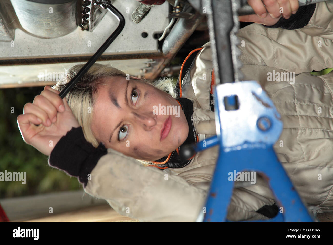Woman fixing her midget race car - Stock Image