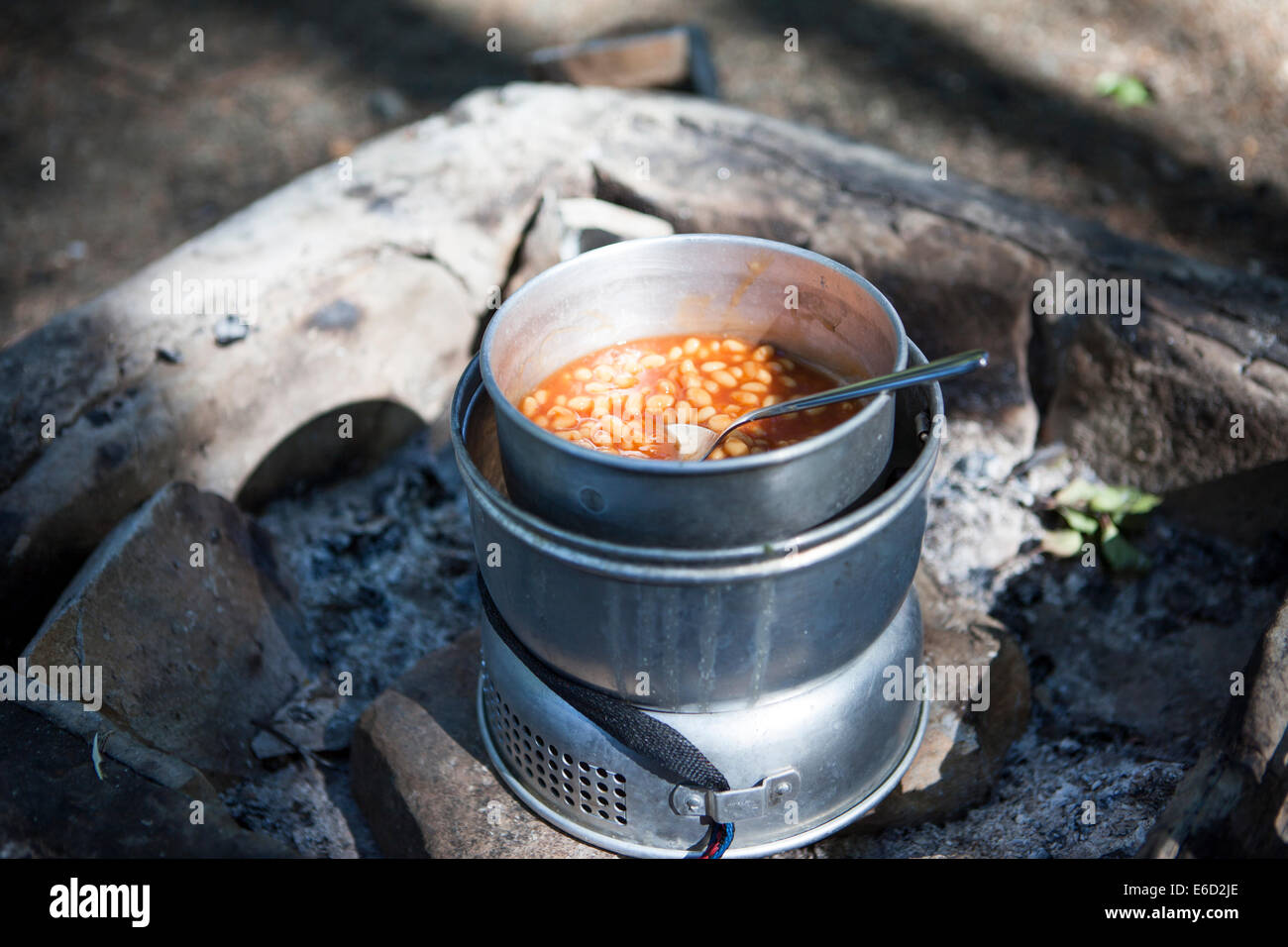 Camping kitchen with baked beans outdoors in nice sunlight. - Stock Image