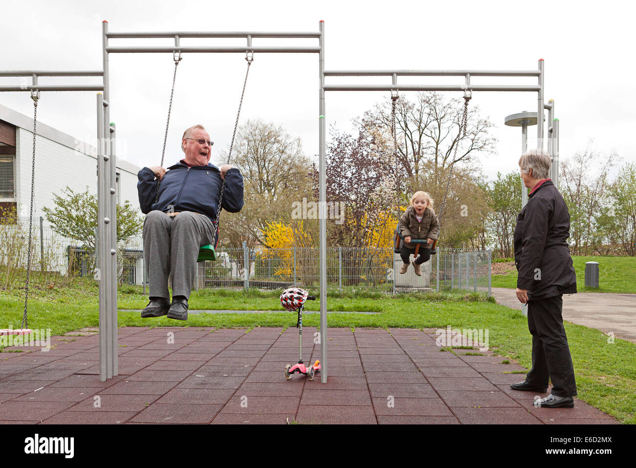 Grandfather and his granddaughter, 3 years, playing on swings, grandmother standing next to them - Stock Image