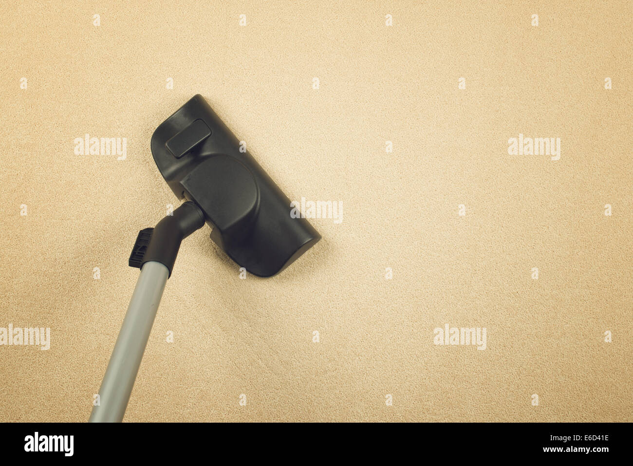 Vacuum Cleaner sweeping Brand New Carpet. Housework and home hygiene. - Stock Image
