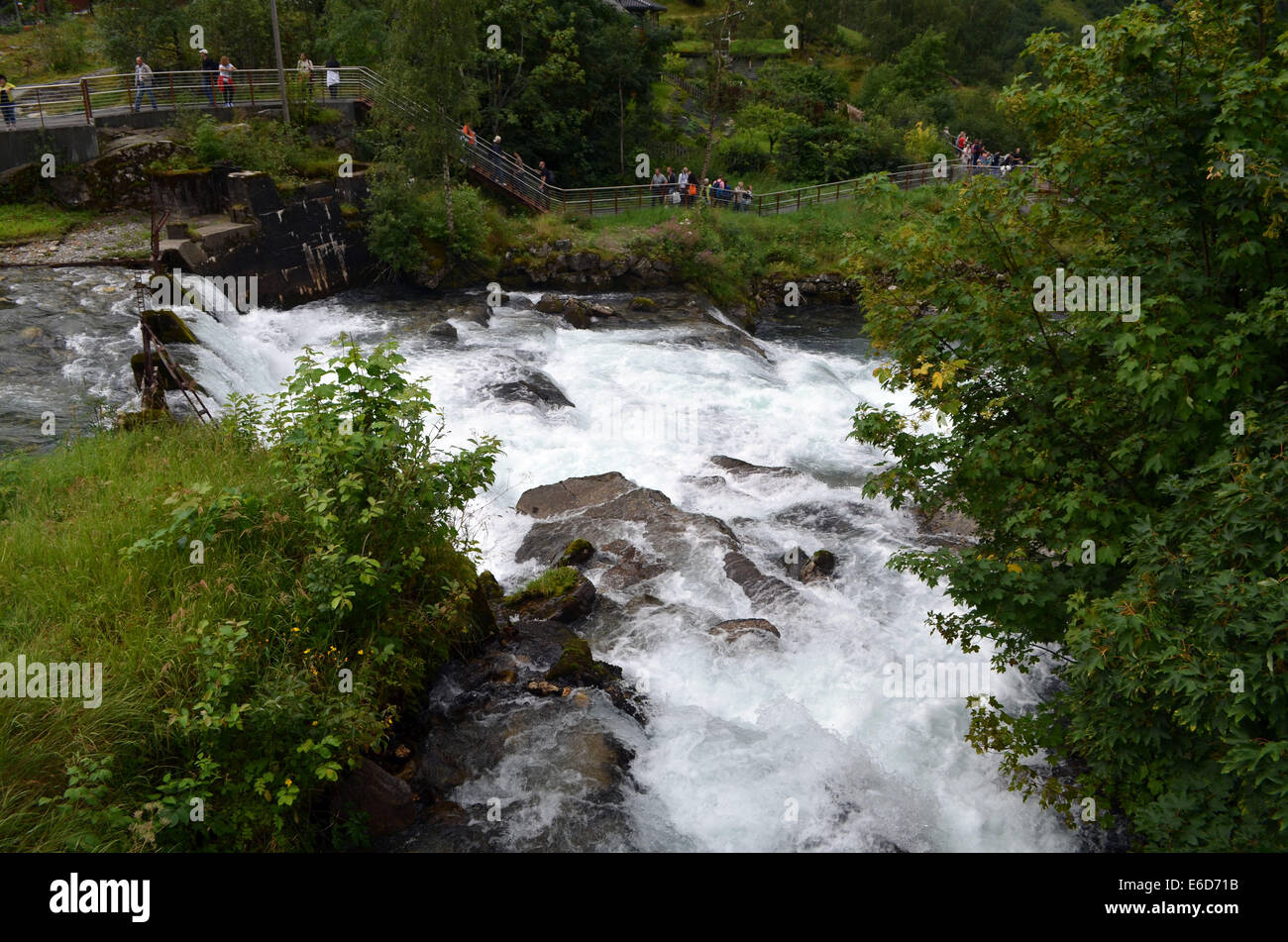 Geiranger Fford. A fast flowing stream runs alongside the cafe and buildings at Geiranger fjord. - Stock Image