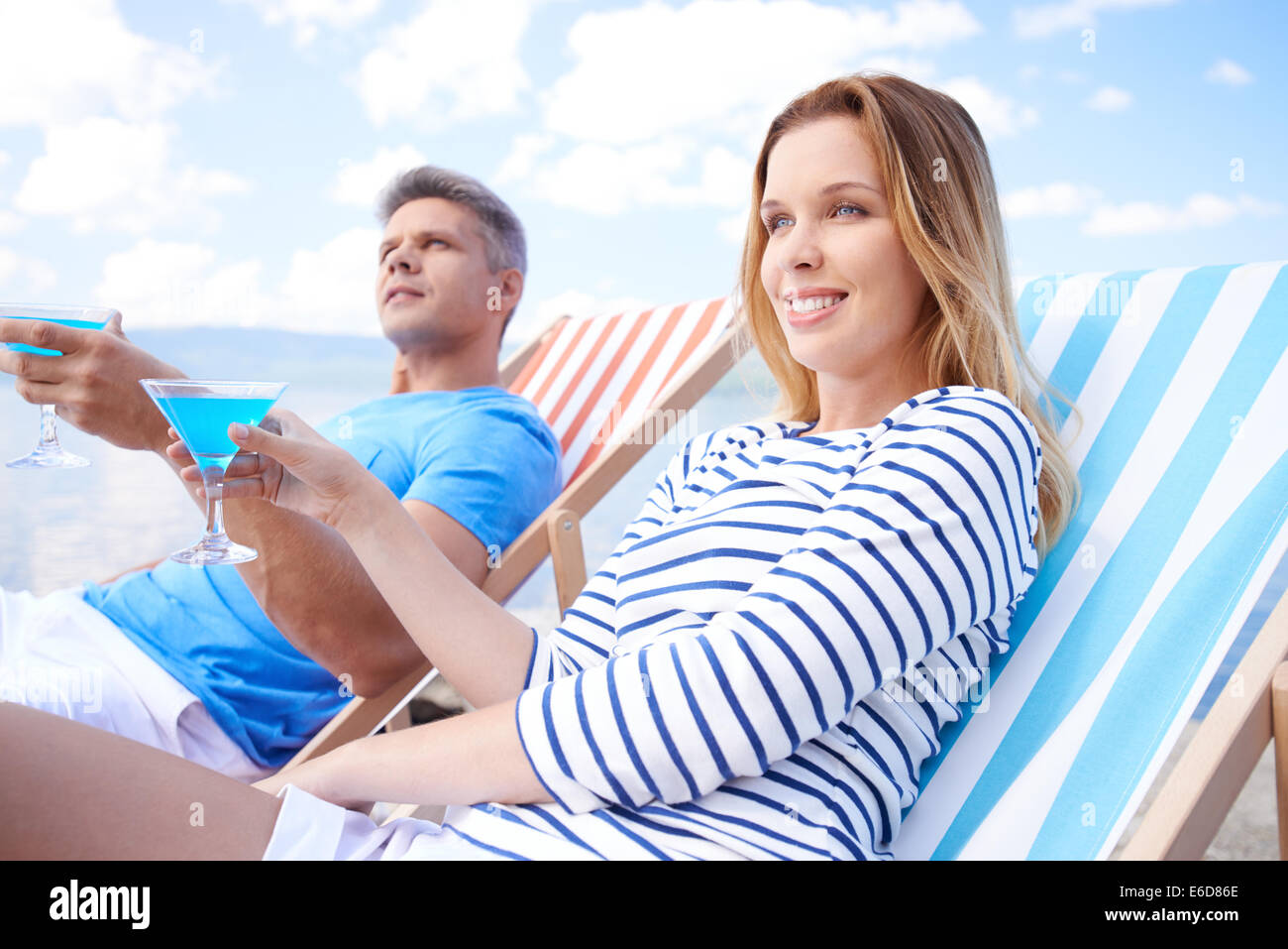 Couple resting in deck chair with martini - Stock Image