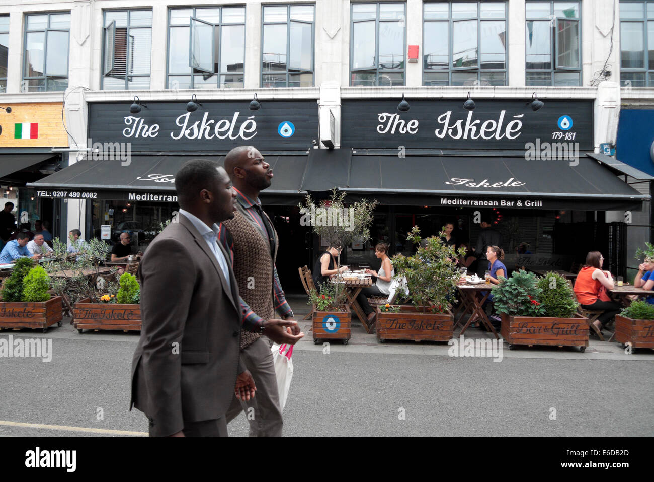Two men walking past people eating al fresco at The Iskele Mediterranean Bar & Grill in Whitecross Street London - Stock Image
