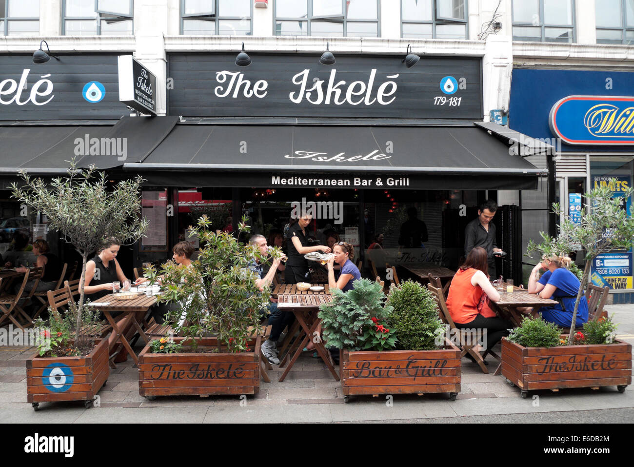 The Iskele Mediterranean Bar and Grill on Whitecross Street people eating at outdoor tables in summer London E1 - Stock Image