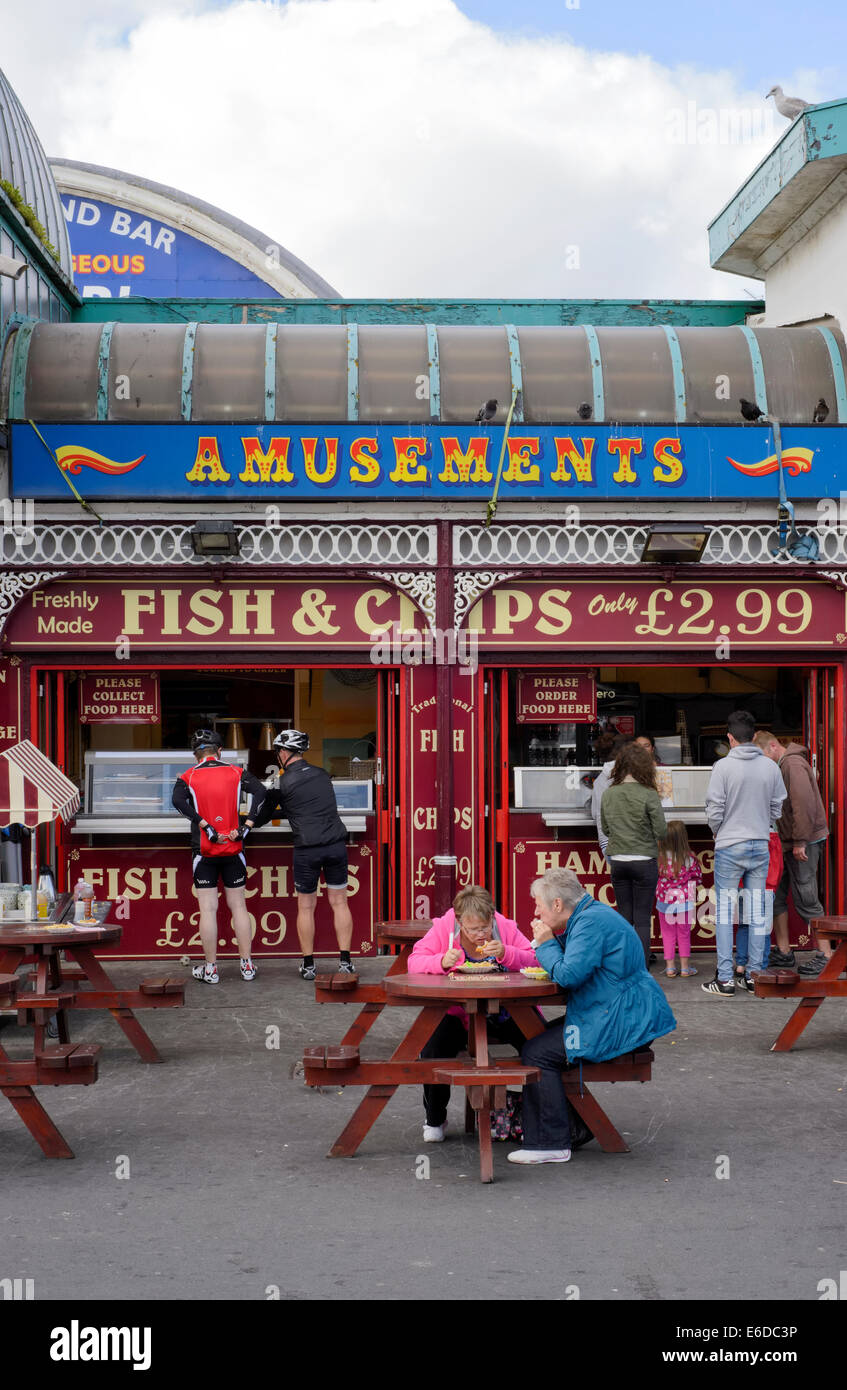 Tourists enjoying fish and chips on Central Pier in Blackpool, Lancashire - Stock Image