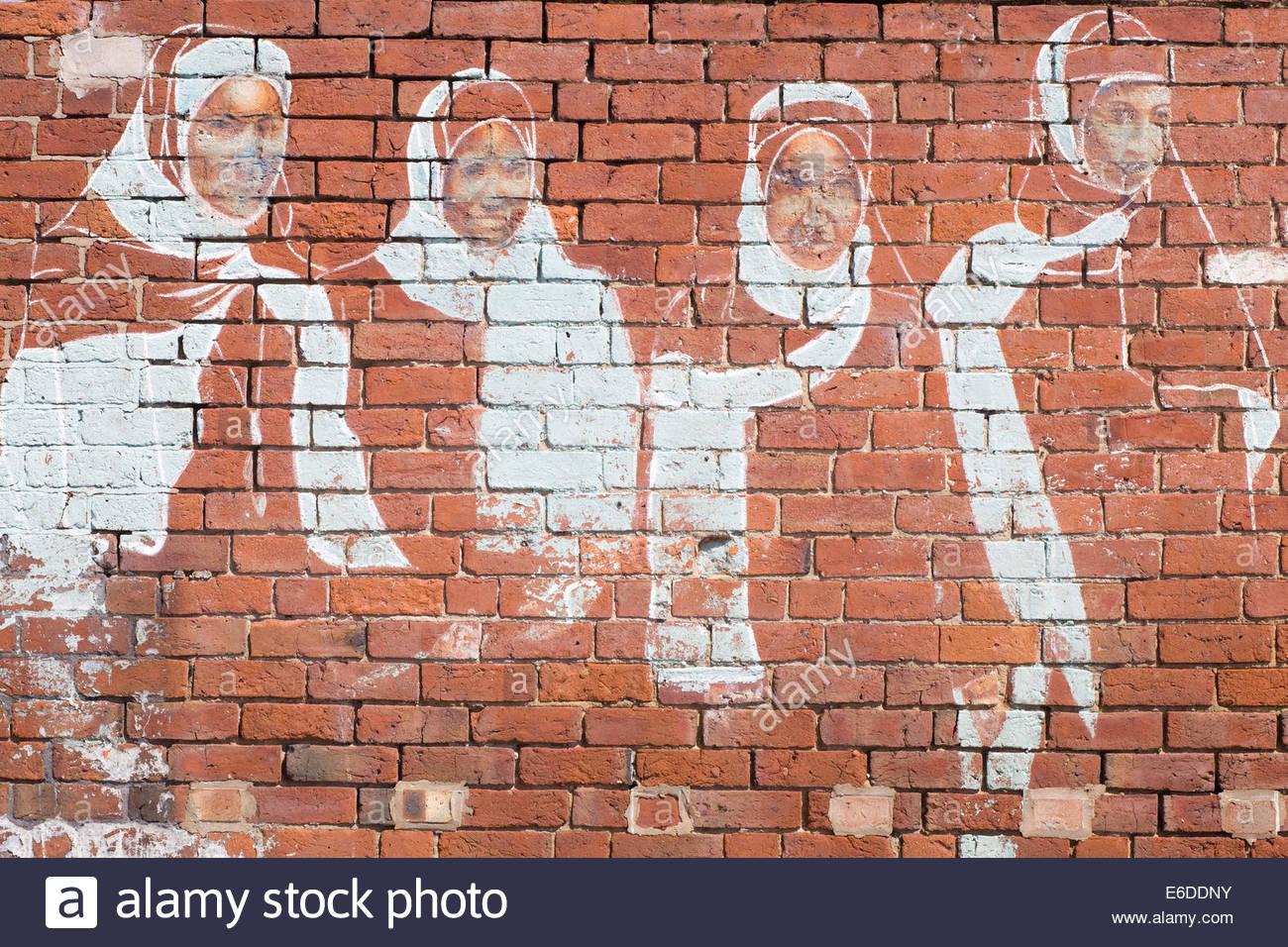 Street Art Graffiti of Muslim Women wearing hijabs Traditional Clothing - Stock Image