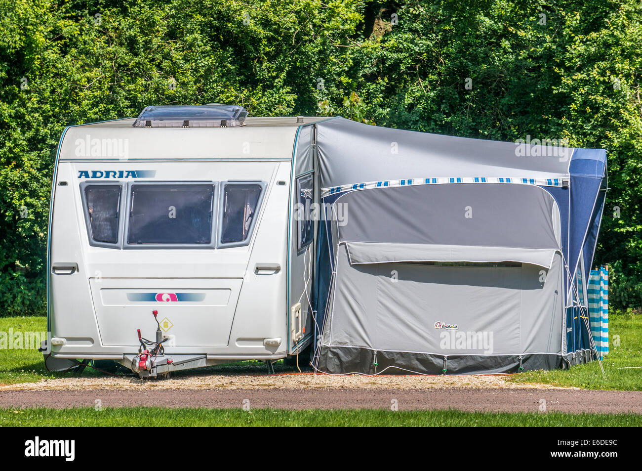 A silver Adria caravan and matching awning on a Caravan Club campsite pitch in England, UK. - Stock Image