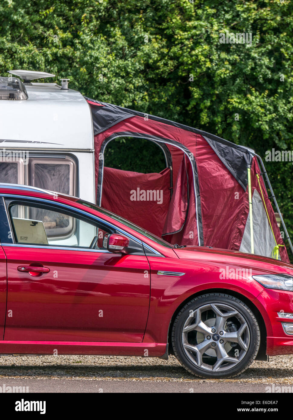A maroon awning and matching car on a caravan Caravan Club campsite pitch in England, UK. - Stock Image