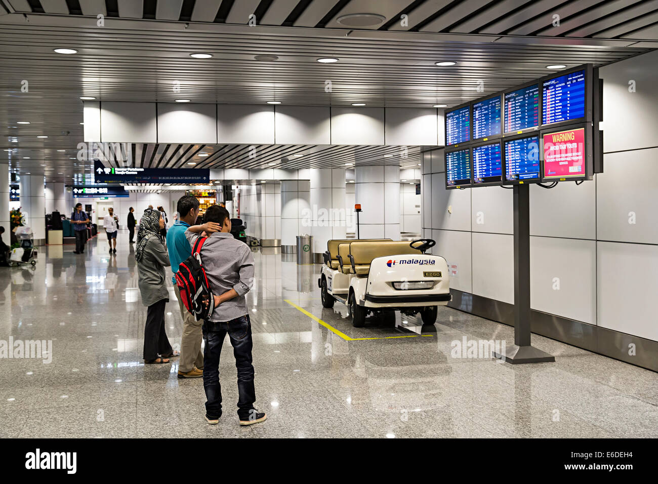 People in transit looking at information screens in airport, Miri, Malaysia - Stock Image
