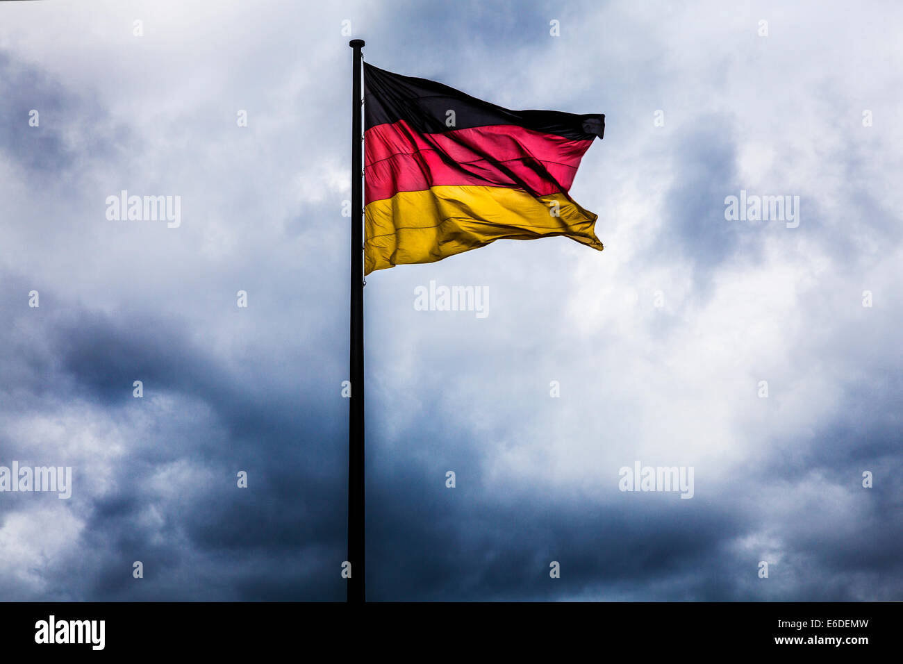 Storm clouds gathering behind the German flag, symbolic of political crisis, war or unrest. - Stock Image