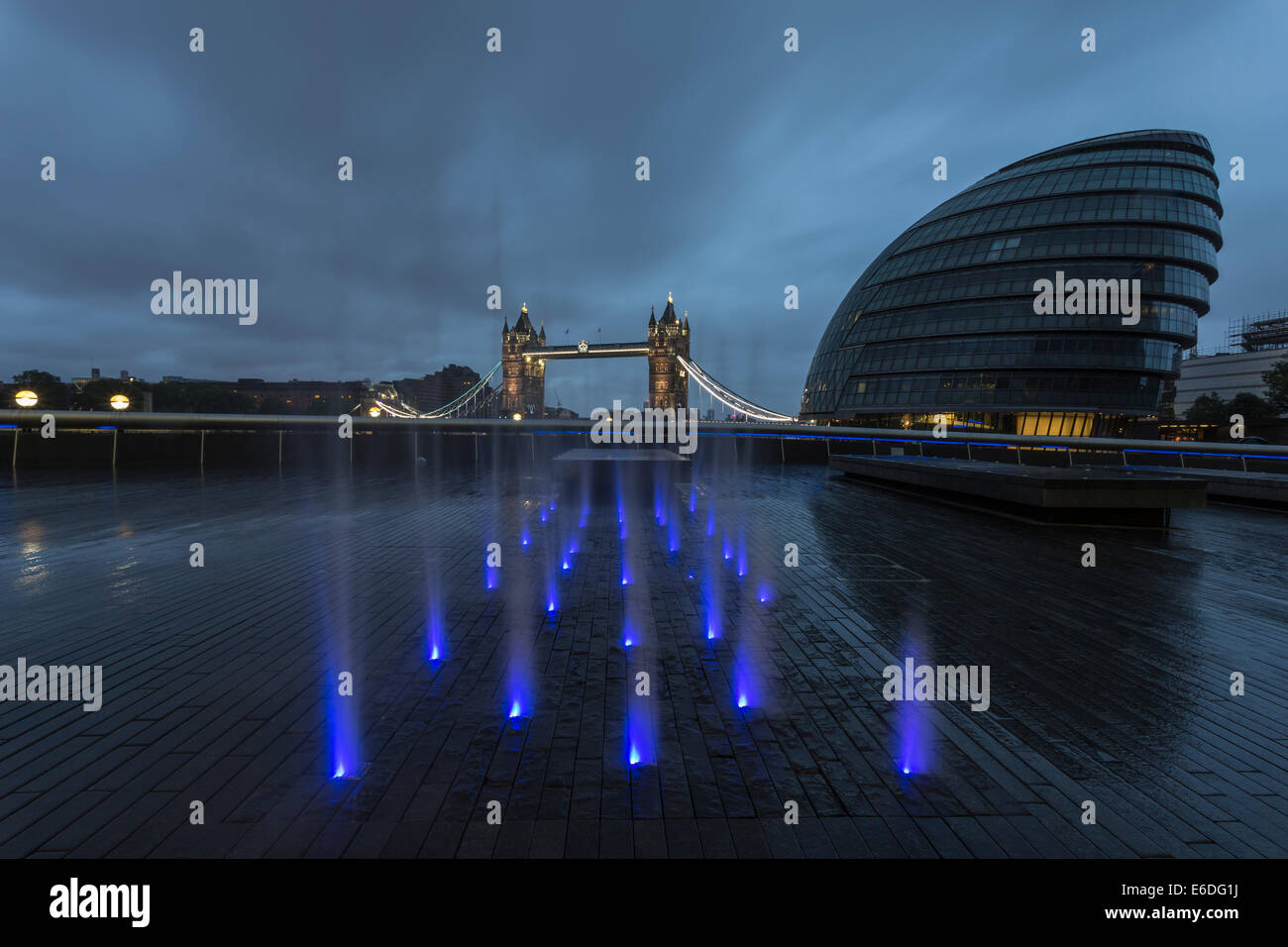 Illuminated fountain in the early morning light with City Hall and Tower Bridge, London, England, United Kingdom Stock Photo