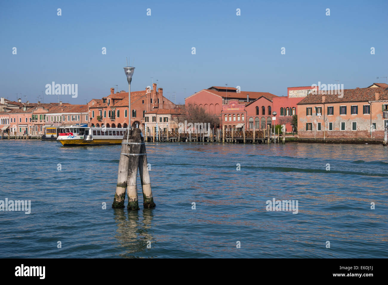 A vaporetto water bus leaves a landing on the Island of Murano in the Venetian Lagoon. - Stock Image