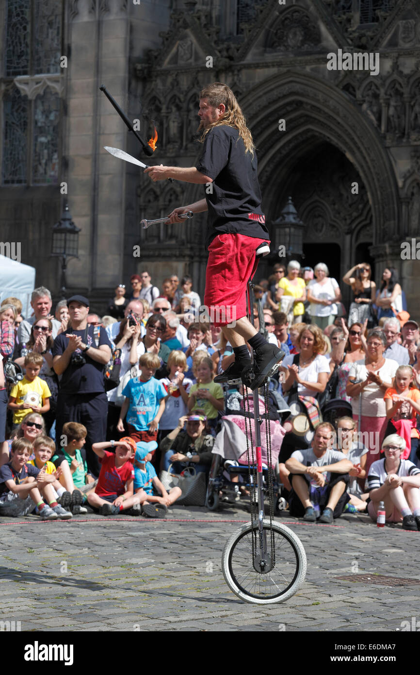Street Performer Mullet Man juggling on a unicycle during the Edinburgh Festival Fringe, Scotland, UK - Stock Image