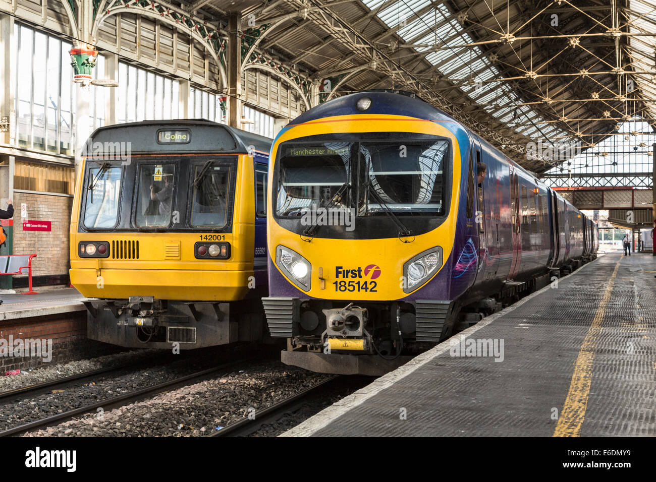 Diesel Multiple Units Class 185 of First Group and Class 142 of Northern Rail standing side-by-side at Preston Railway - Stock Image