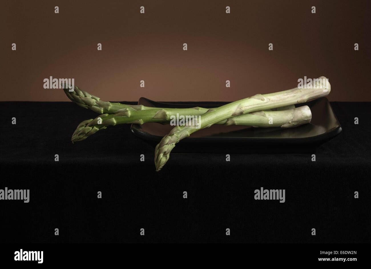 Asparagus in black dish on dark tablecloth - Stock Image