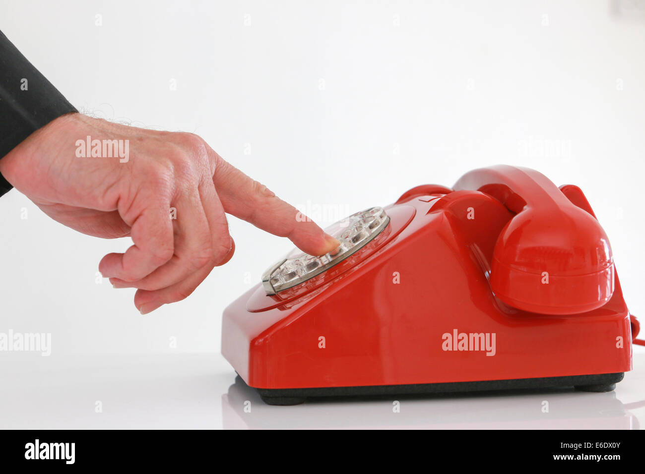 Red retro telephone, man dialing. - Stock Image