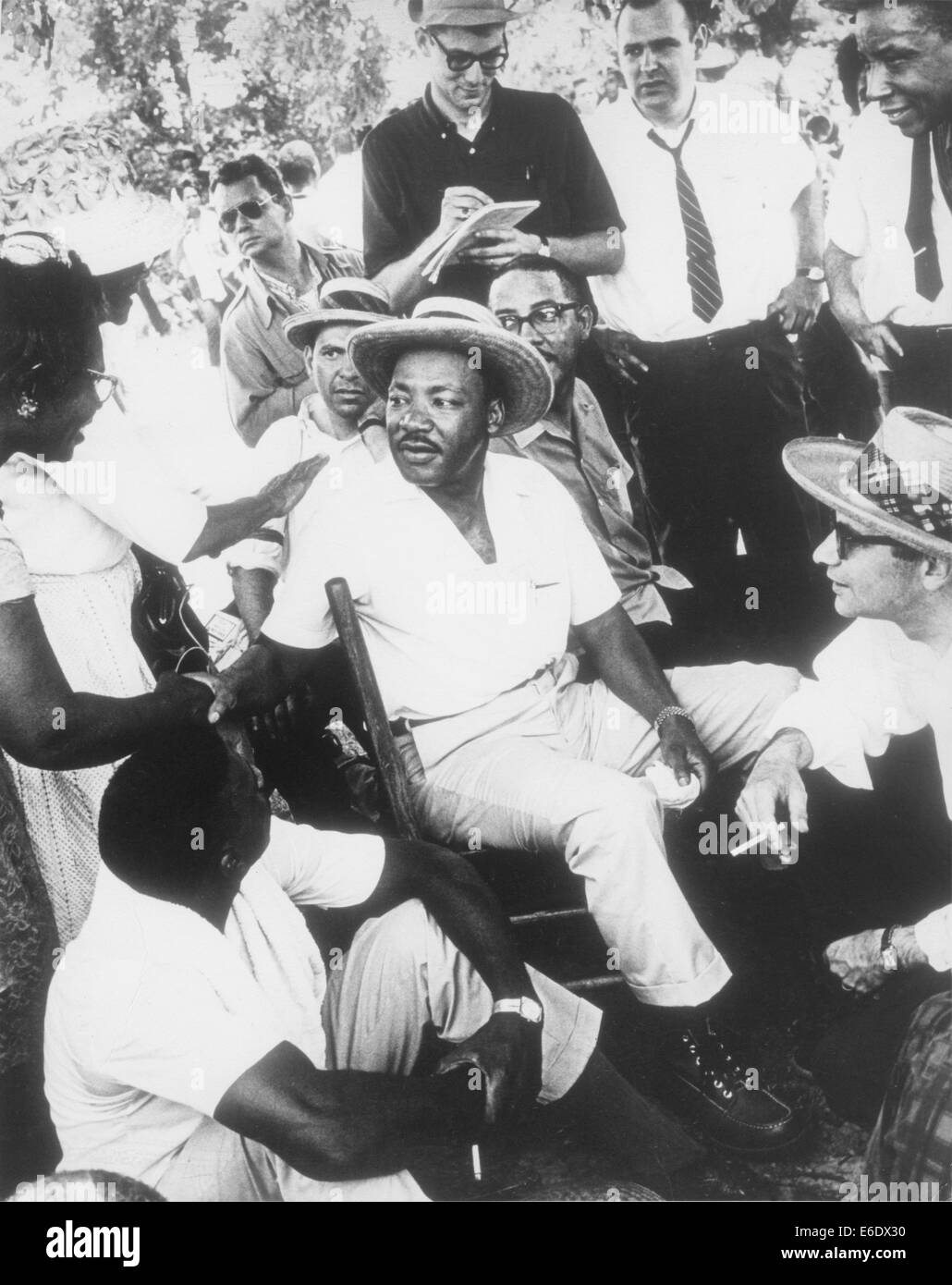 Martin Luther King, Jr in Straw Hat Sitting Down with Group of Men While Shaking Hands with Woman, circa 1960's Stock Photo