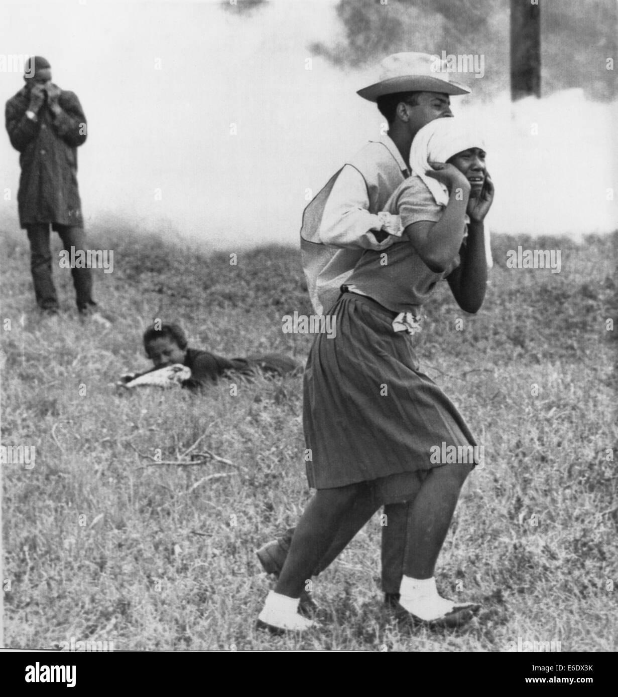 Civil Rights Demonstrator Helping Young Woman After Police Toss Smoke Bombs, Camden, Alabama, USA, 1965 - Stock Image
