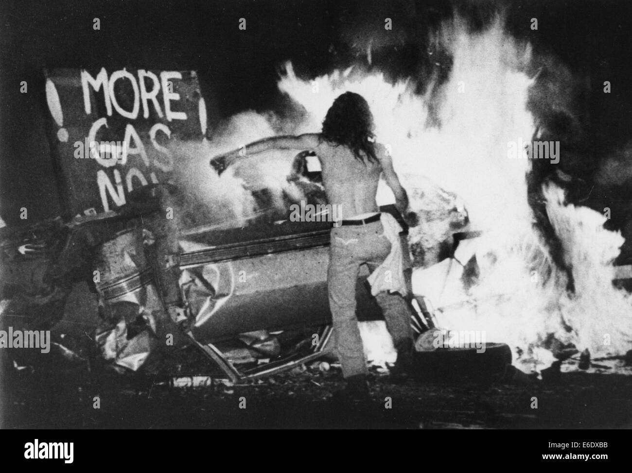 Gas Shortage Demonstrator in Front of Burning Car During Riot at Night, Levittown, Pennsylvania, USA, 1979 - Stock Image