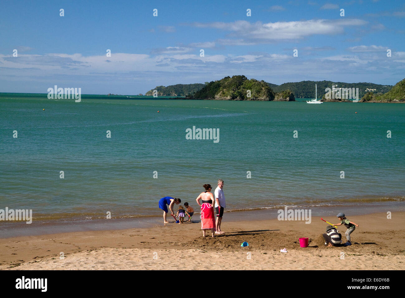 People on the beach at Bay of Islands at the town of Paihia, North Island, New Zealand. - Stock Image