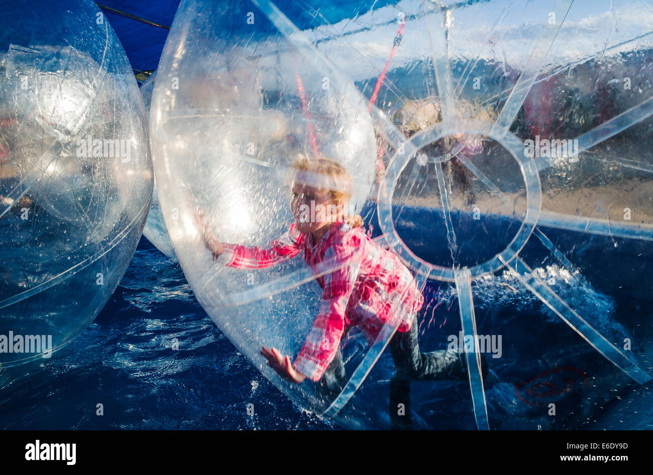 Children play in Water Bubbles, large inflated balls floating in a pool of water, Chaffee County Fair, Colorado, - Stock Image