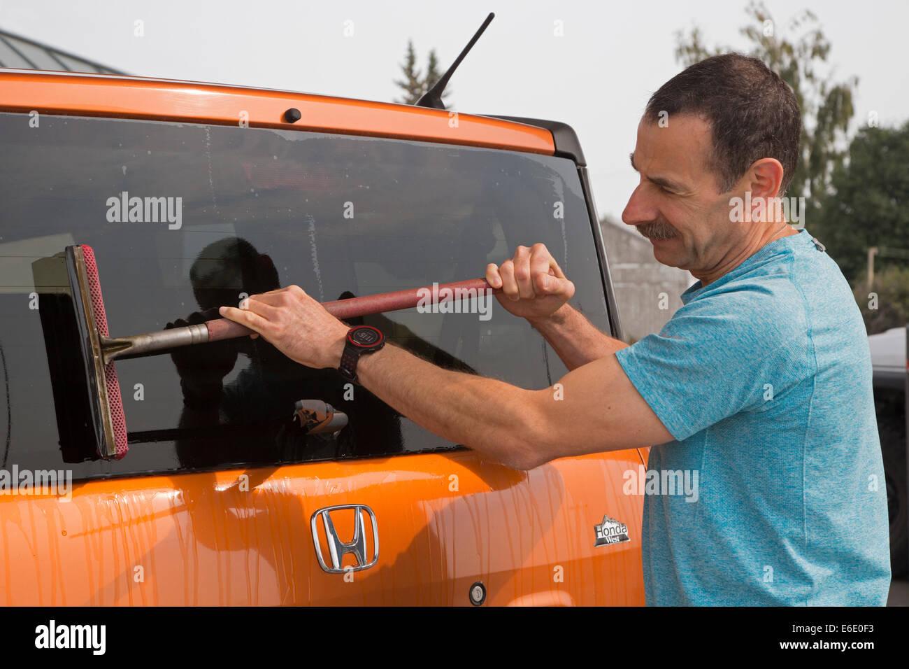 Man washing vehicle windshield at service station - Stock Image