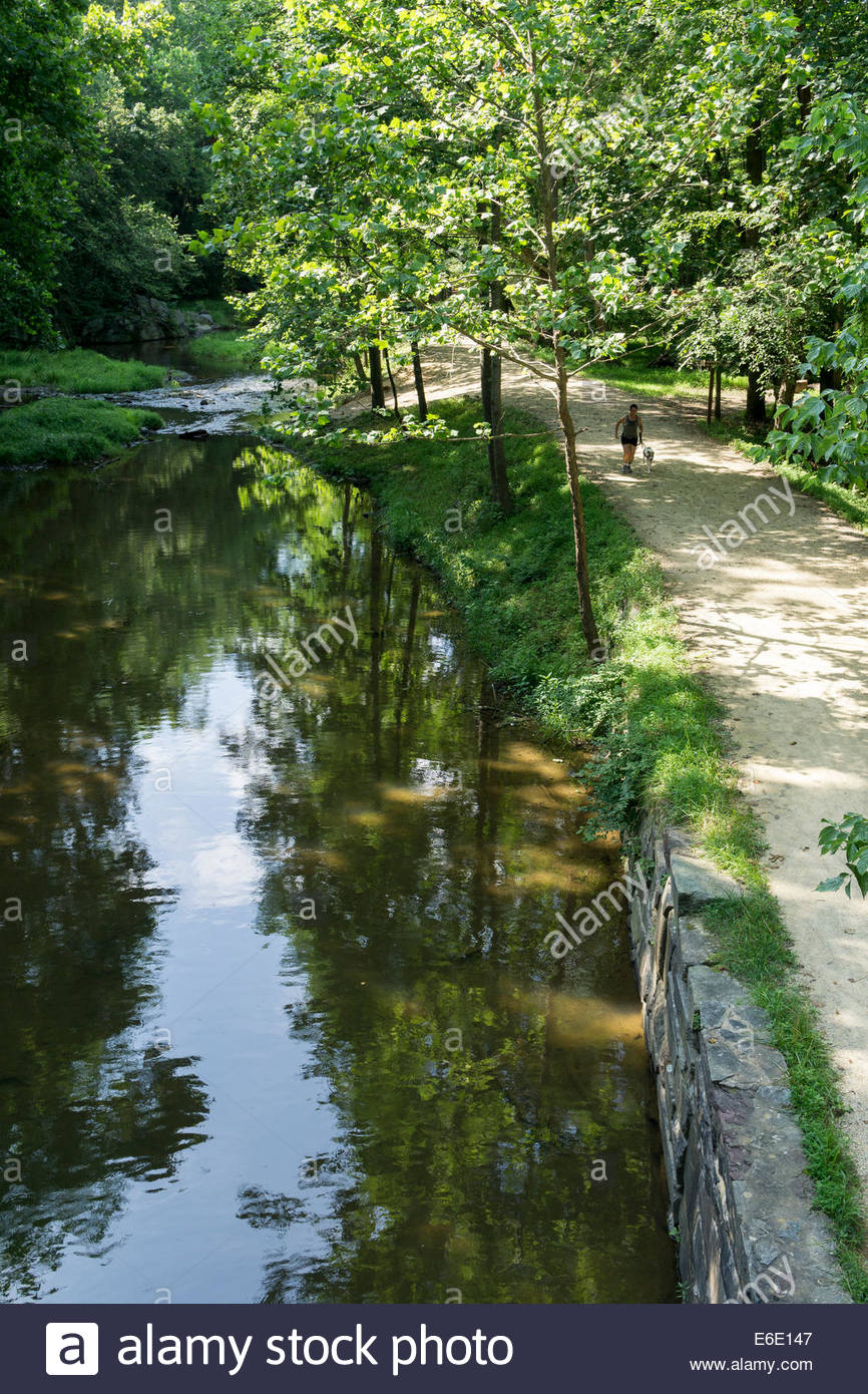 A woman runs with her dog on the C&O Canal towpath in Potomac, Maryland - Stock Image