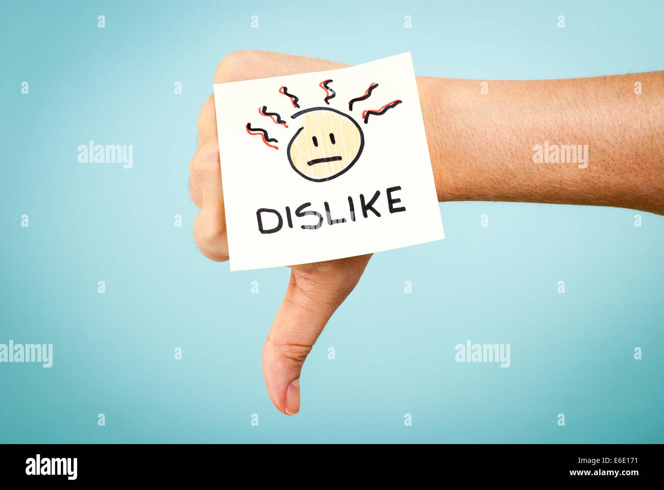 Dislike concept with hand on blue background - Stock Image