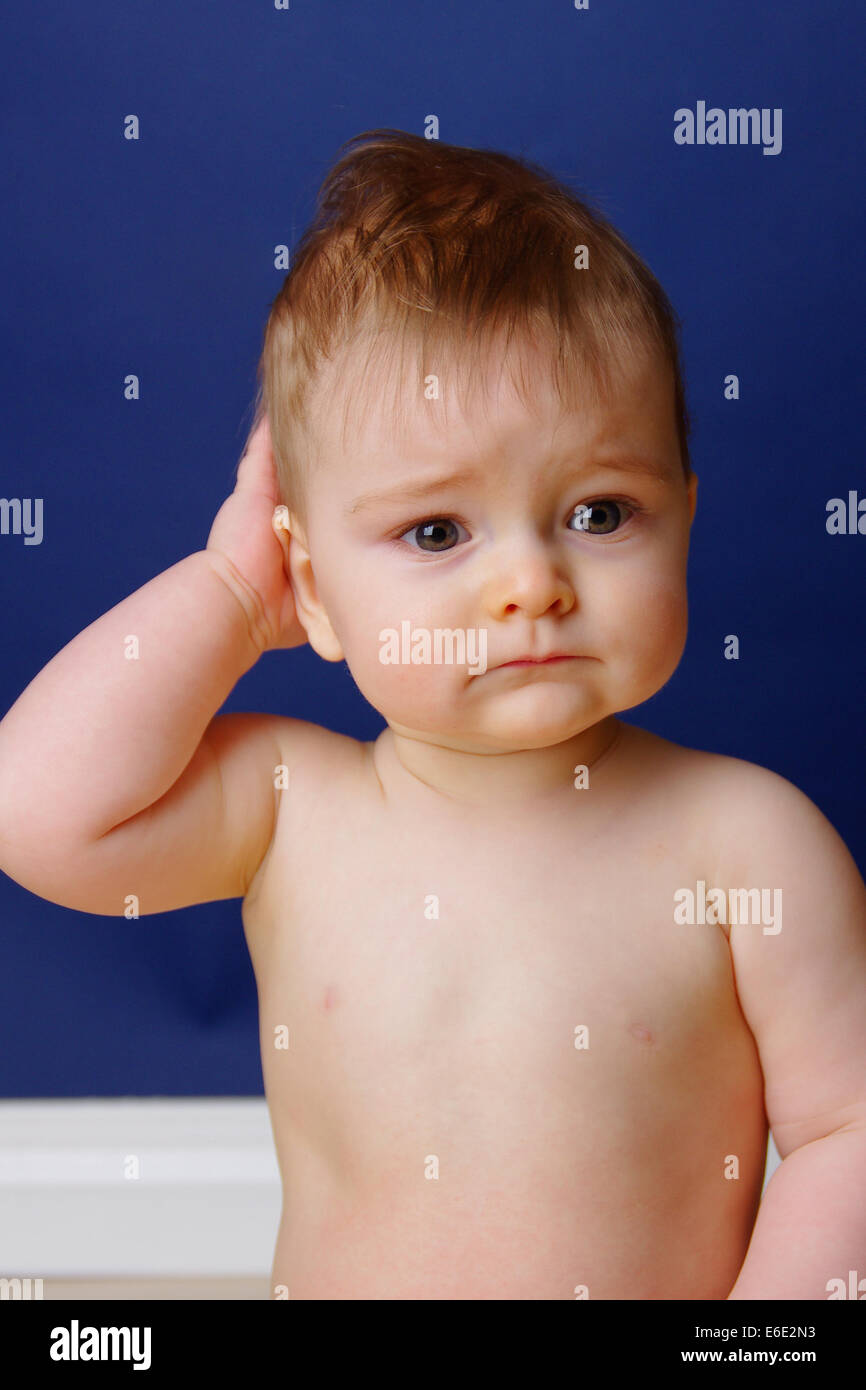9 month old baby looking sad and forlorn stock image