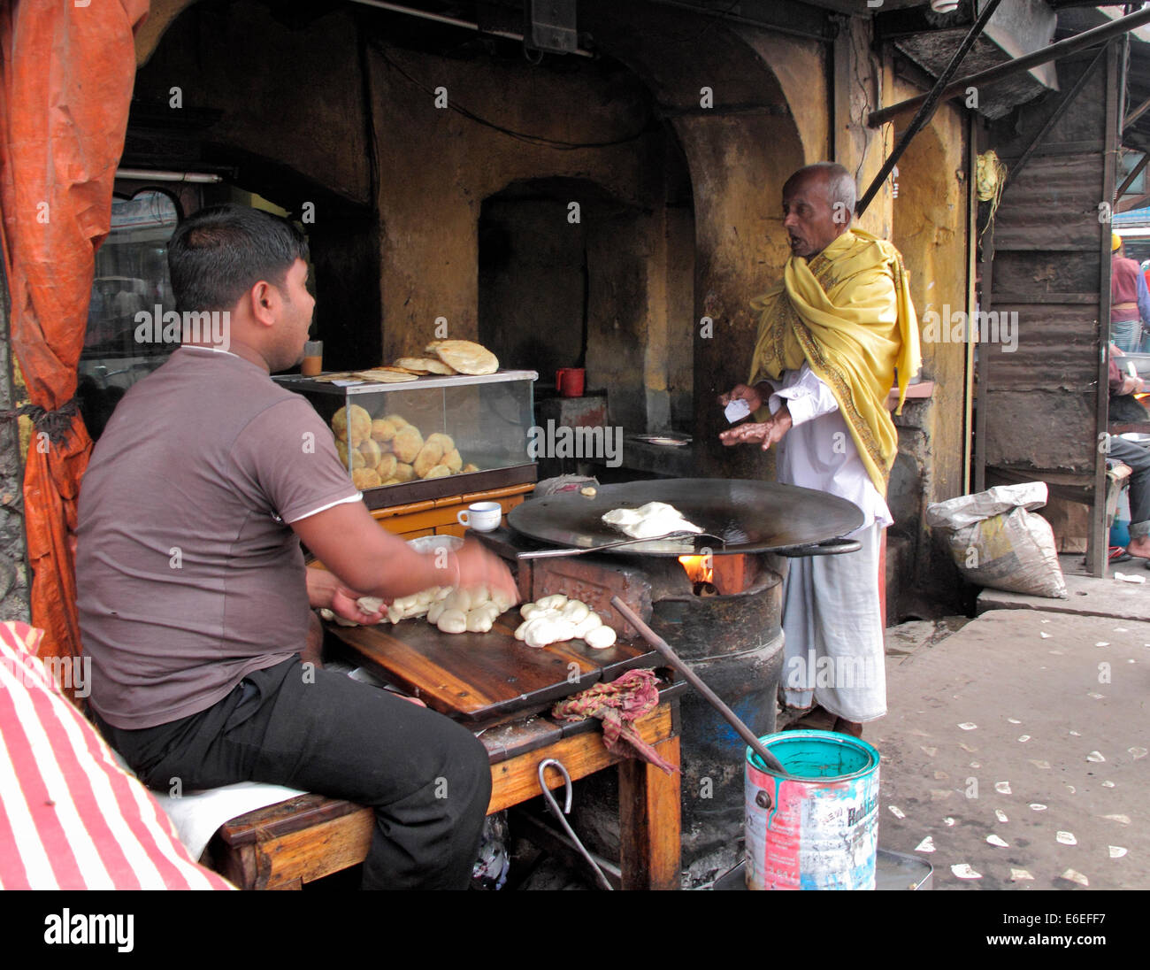 Morning in Bangladesh restaurant, man is warming his hands above hot plate. Cooking on fire, chapati bread,food, - Stock Image