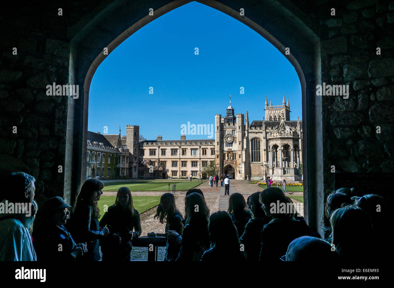 A crowd of tourists looking through a stone archway at Trinity College and the Grand Court, University of Cambridge, - Stock Image
