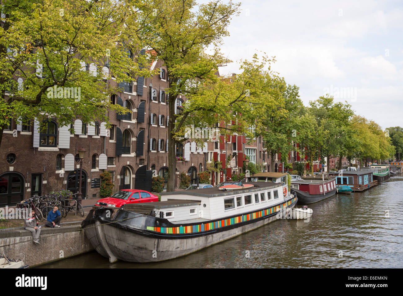 people relaxing at the side of one of the canals (Prinsengracht) in Amsterdam in the Netherlands - Stock Image