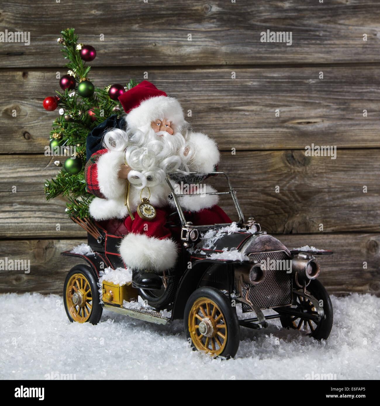 Santa claus in rush with his car: christmas shopping stress. Decoration with old vintage tin toys on wooden background. - Stock Image