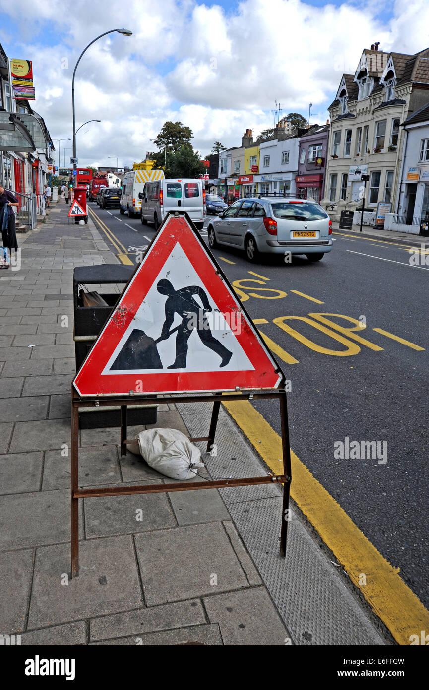 Brighton UK - Men at work roadworks street sign in road - Stock Image