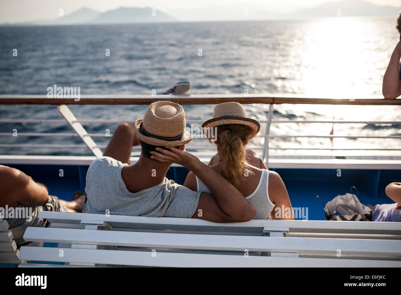 A couple gaze to the sunset as they travel with a ship to Volos on August 21, 2014. - Stock Image
