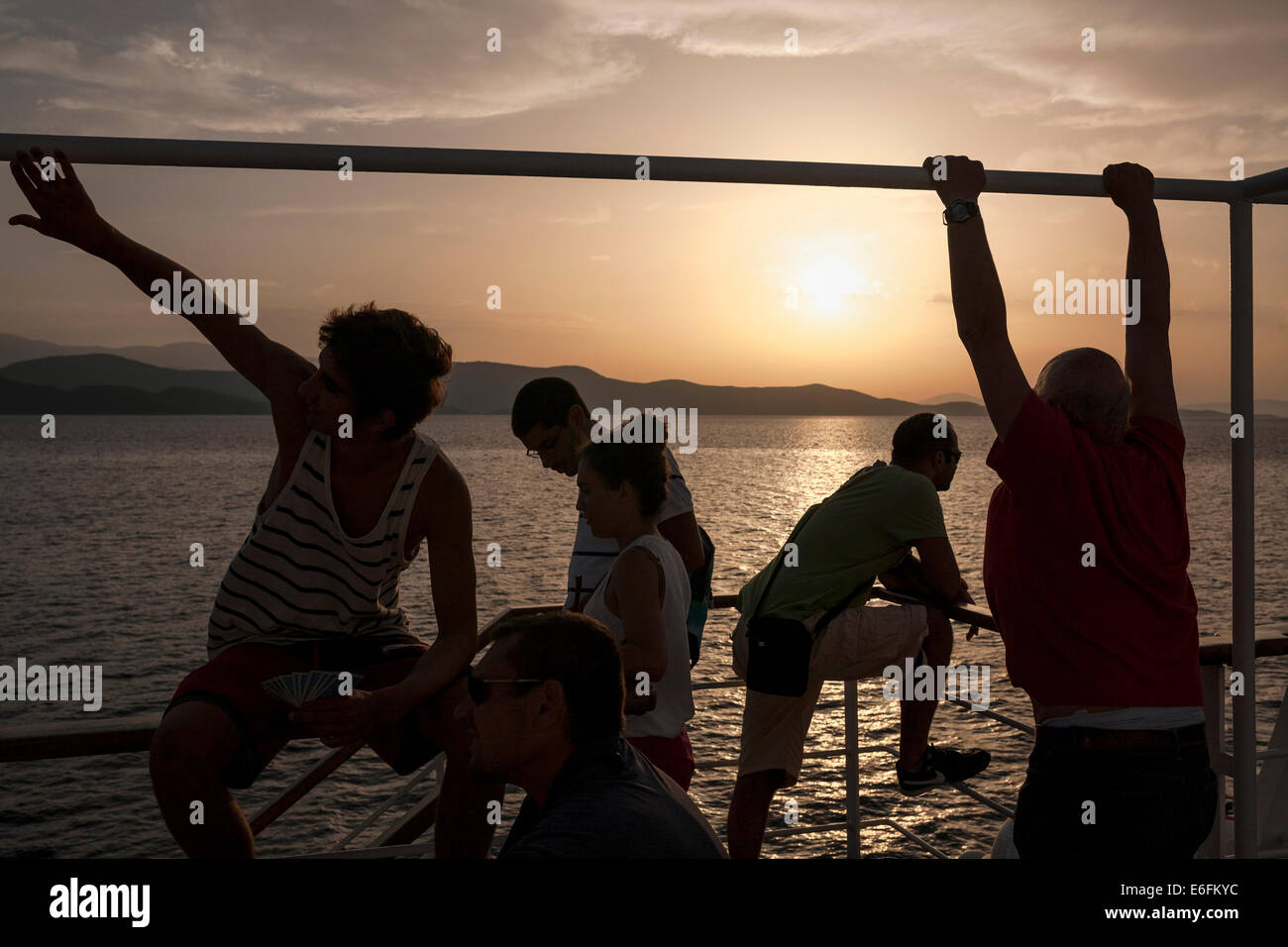 Travelers gaze to the sunset as she travel with a ship to Volos on August 21, 2014. - Stock Image