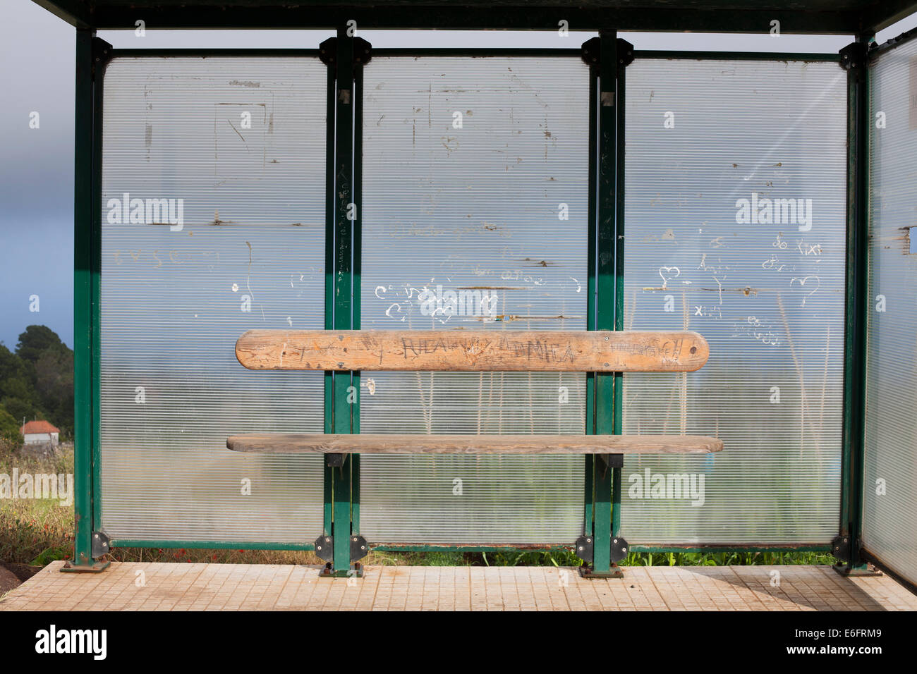 A bus shelter and a wooden bench. - Stock Image
