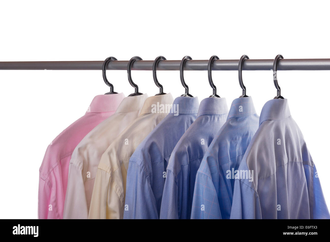 Seven mens shirts hanging on a clothing rail. - Stock Image