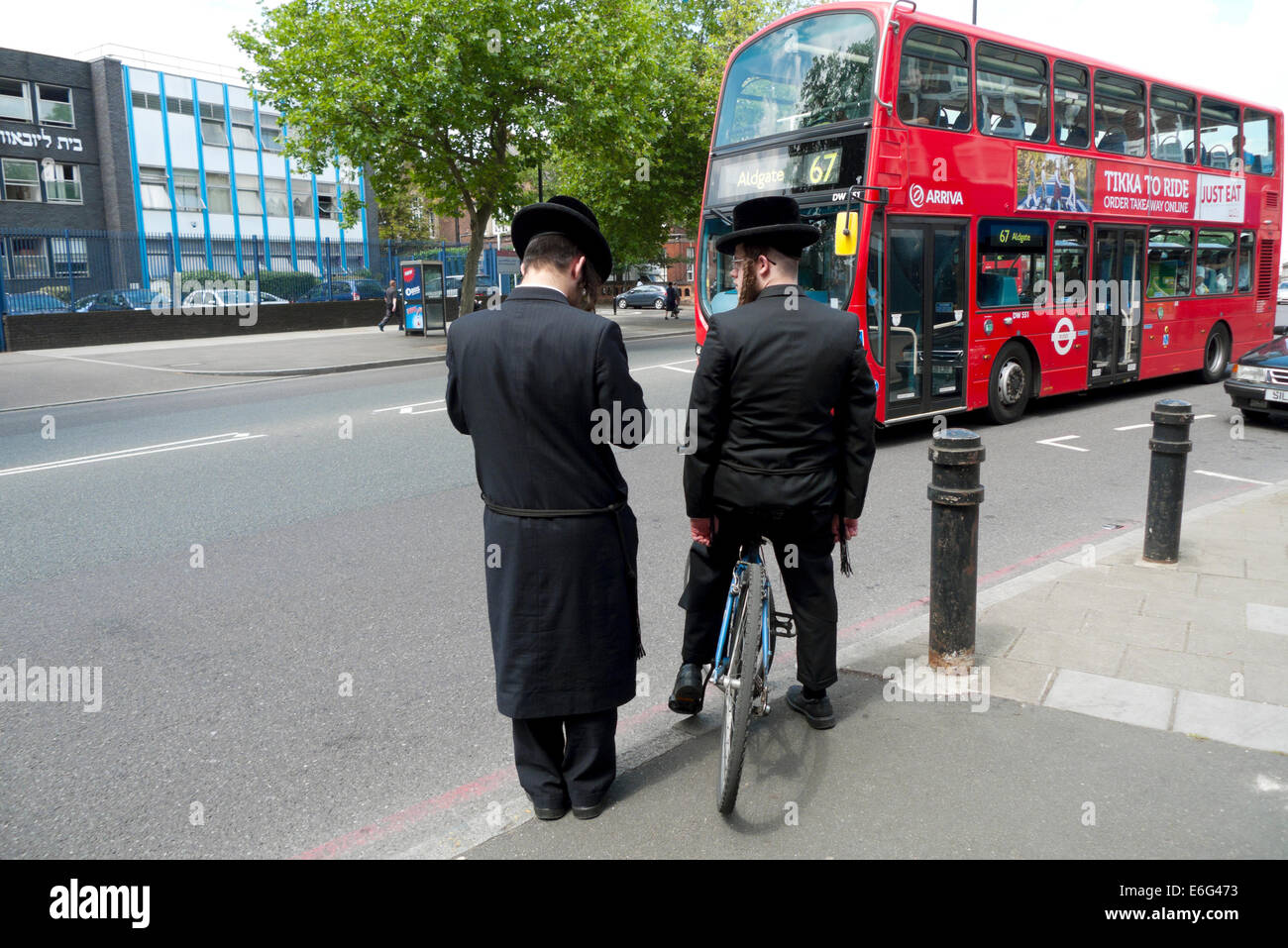 Young Orthodox Jewish men with bicycle wait for double-decker red bus traffic to cross road in Stamford Hill area - Stock Image