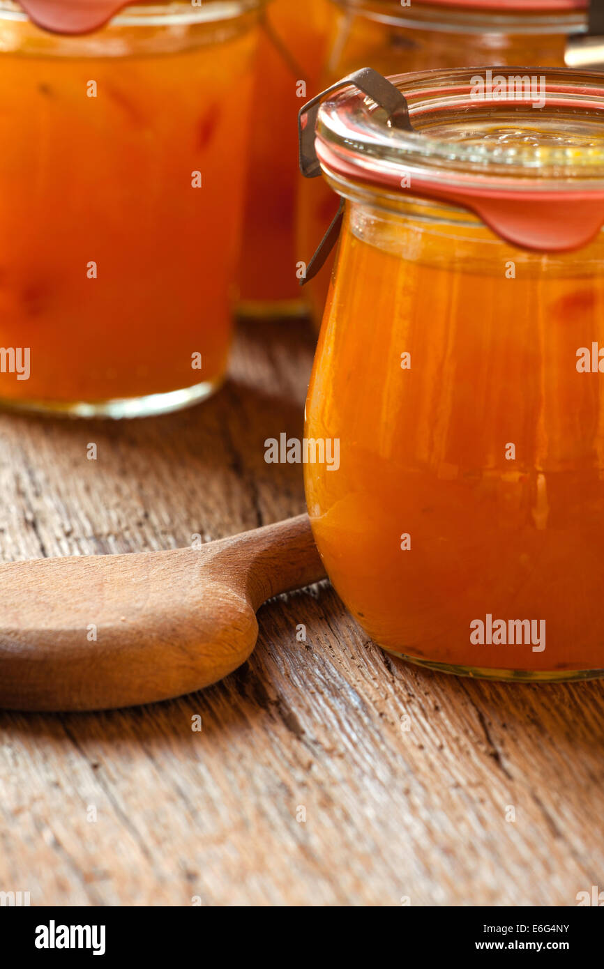 Homemade melon jam in a preserving jar on rustic wooden background with copy space - Stock Image