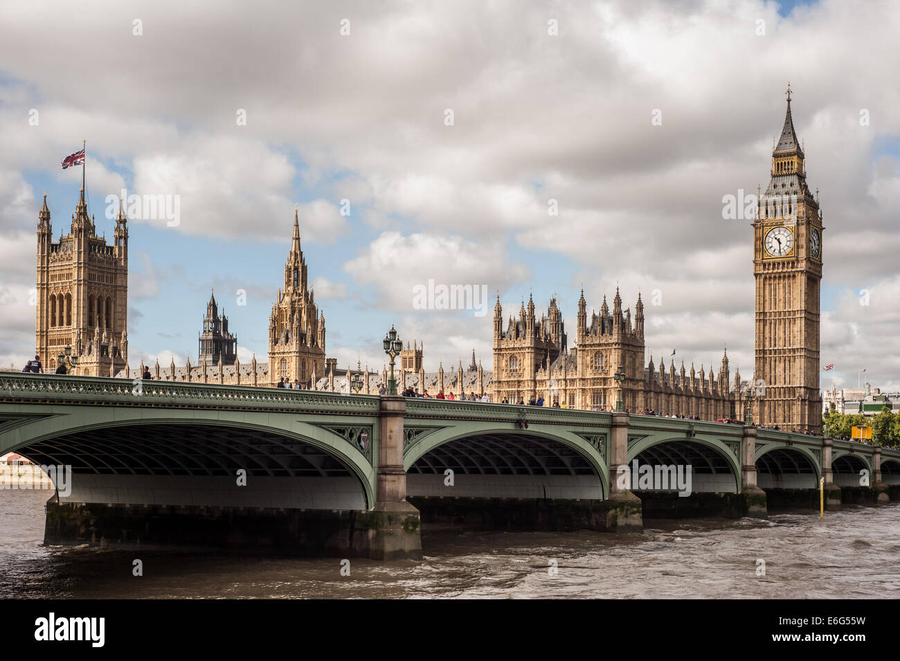 The Houses of Parliament, the Big Ben with people crossing Westminster Bridge in London on a cloudy day - Stock Image
