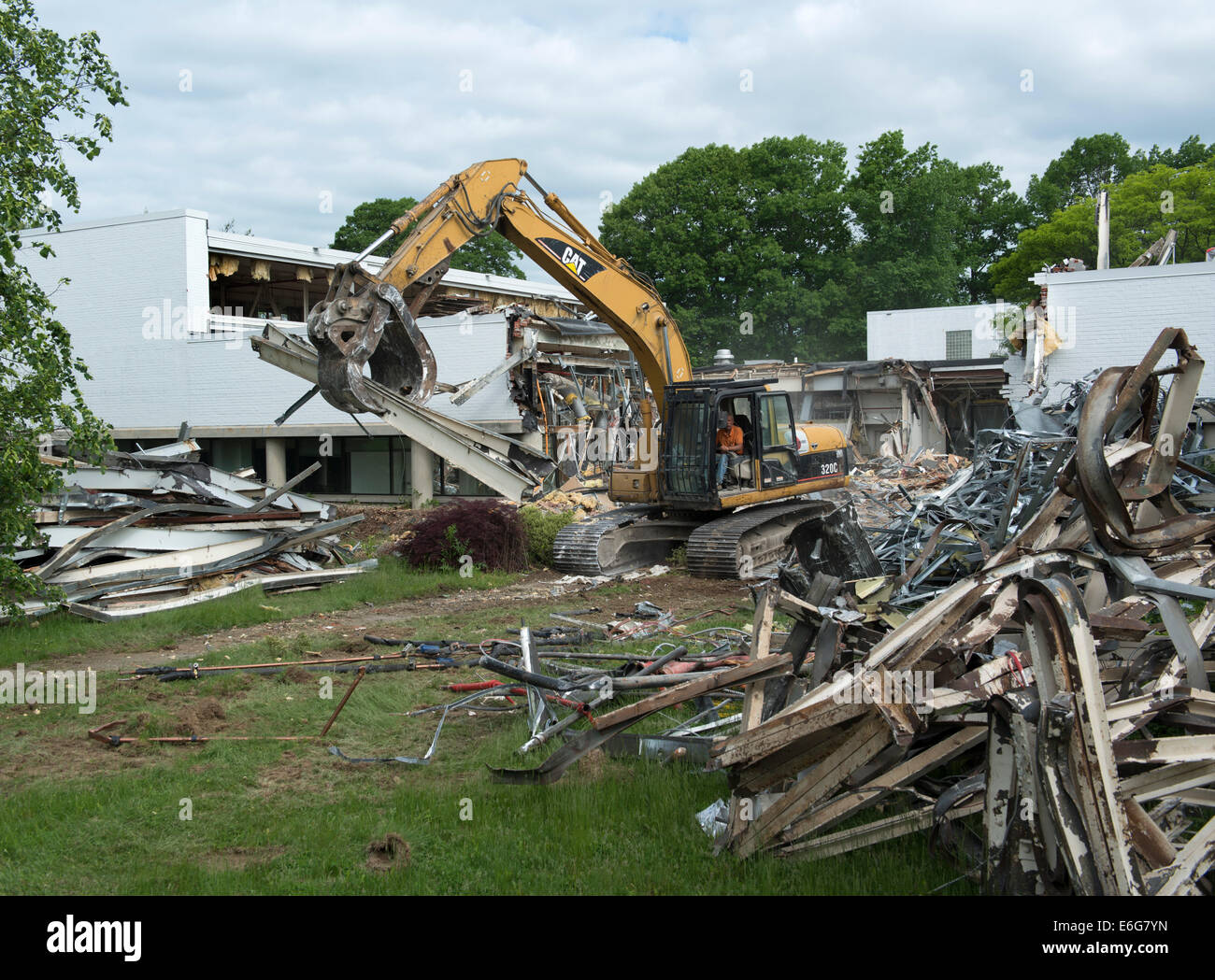 Excavator with grapple doing demolition work on office building in Norwalk, CT.  Materials sorted for recycling. - Stock Image