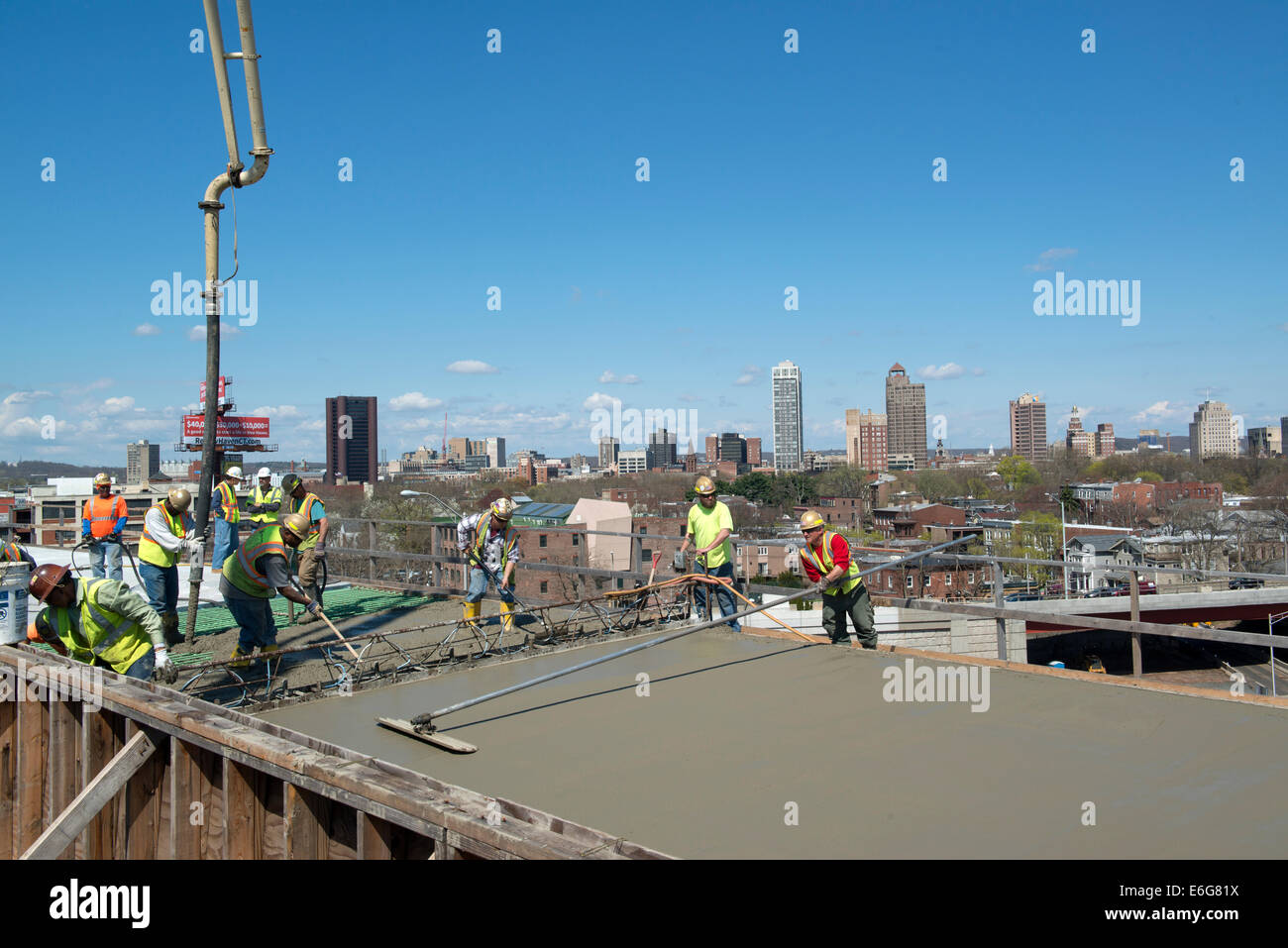 Workers pouring concrete and using bull float to smooth concrete for new highway overpass on I-95 Harbor Crossing - Stock Image
