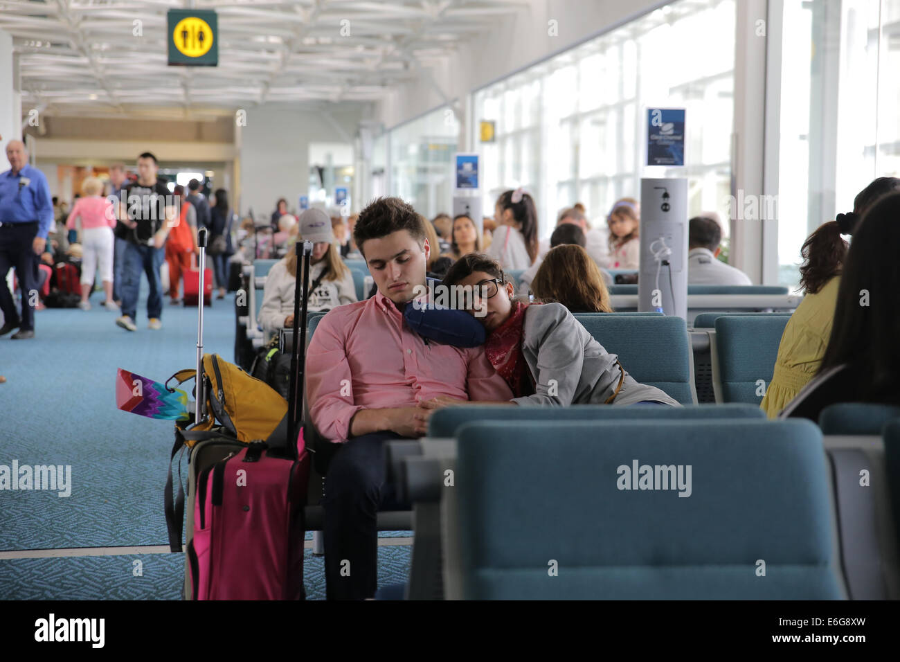 tired exhausted passenger lapping inside airport boarding gate area - Stock Image