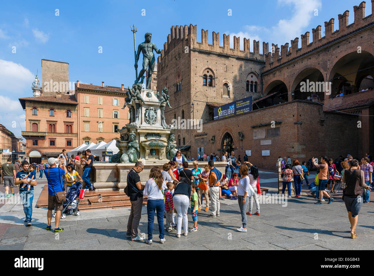 Tourists gathered round the Neptune Fountain with the Palazzo Re Enzo behind, Piazza del Nettuno, Bologna, Emilia - Stock Image