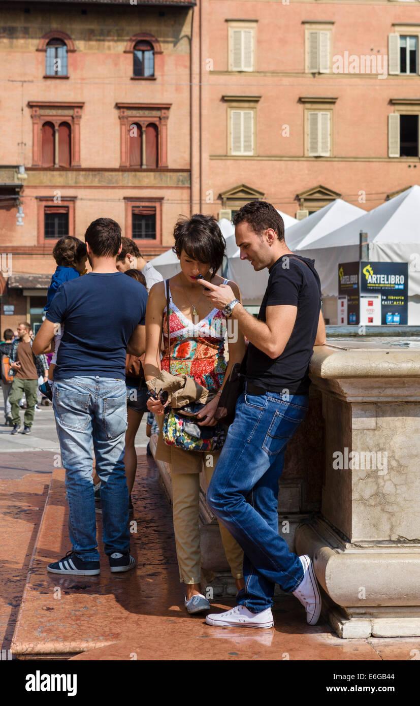 Young couple standing by the Neptune Fountain in Piazza del Nettuno, Bologna, Emilia Romagna, Italy - Stock Image