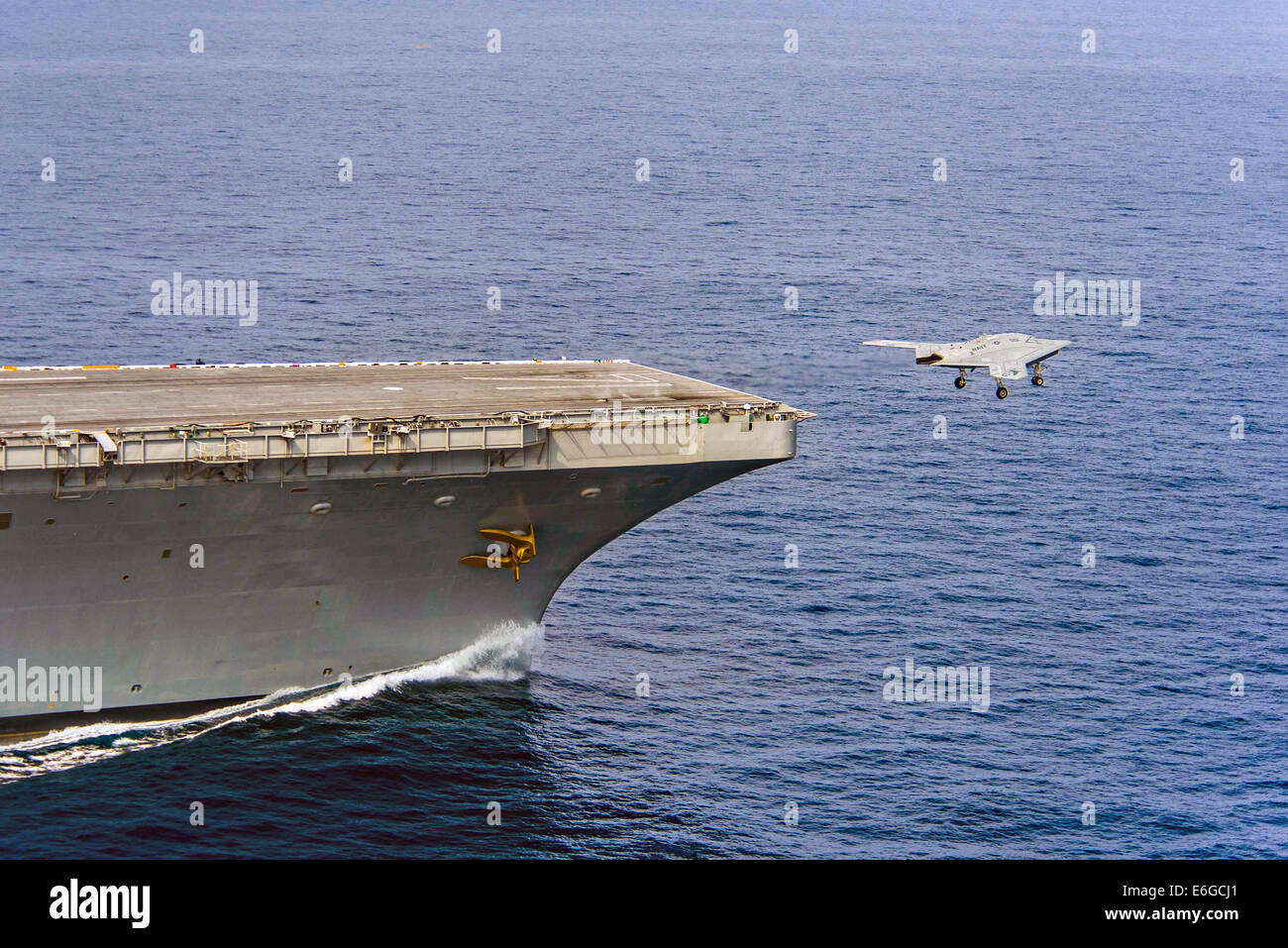 The US Navy X-47B autonomous stealth unmanned aerial vehicle takes off from the flight deck of the aircraft carrier - Stock Image