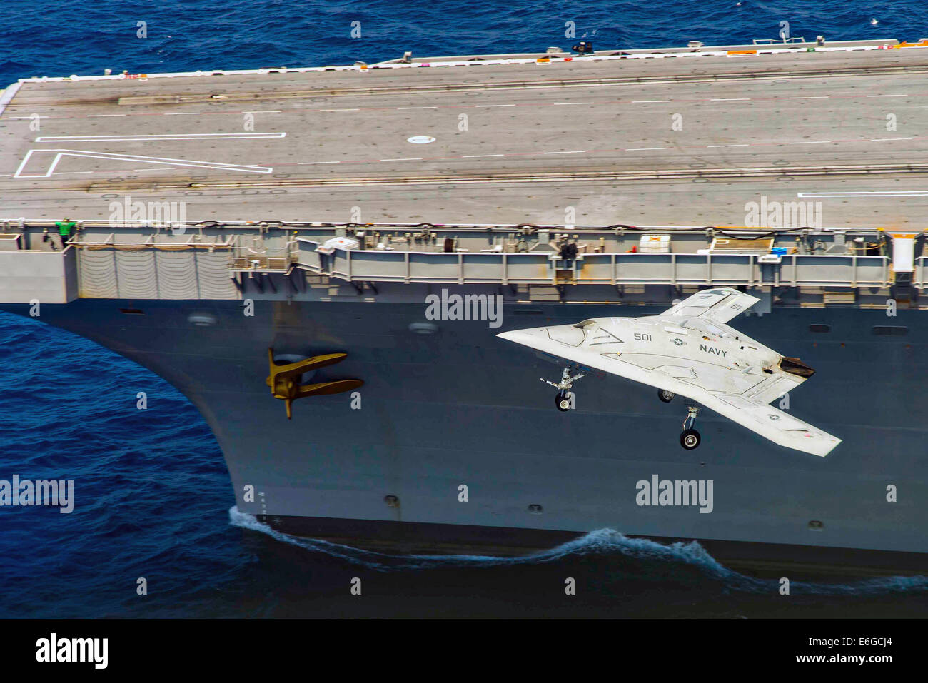 The US Navy X-47B autonomous stealth unmanned aerial vehicle flies past the flight deck of the aircraft carrier - Stock Image