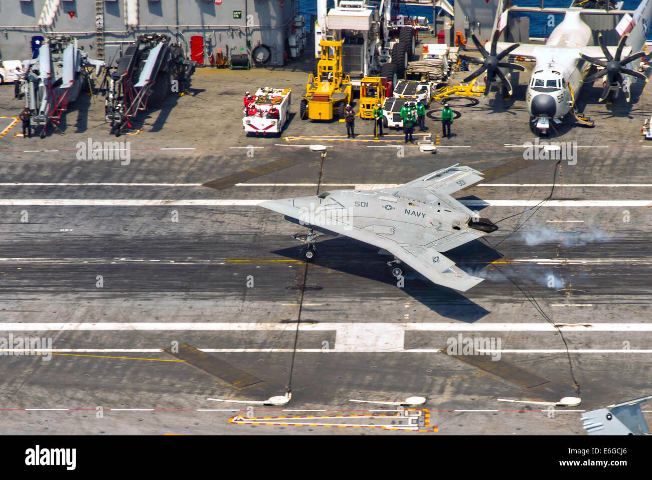 The US Navy X-47B autonomous stealth unmanned aerial vehicle performs an arrested landing on the flight deck of - Stock Image
